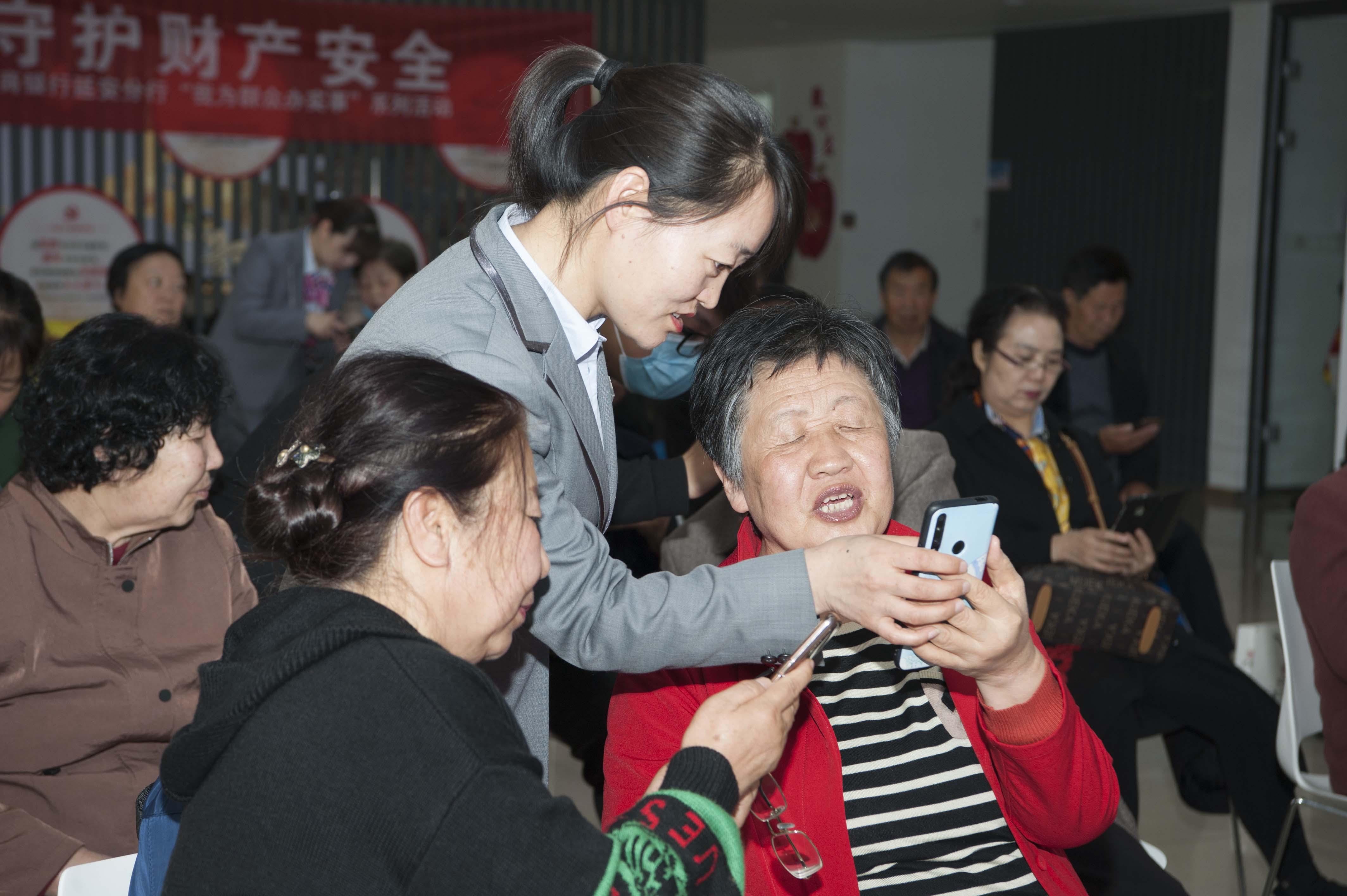 电信人员在一对一指导老年人使用智能手机.jpg